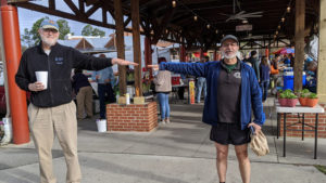 Two men stand beside each other with arms extended sideways, but not touching, to demonstrate proper social distancing at a farmers market during the COVID-19 pandemic. Photo by Debbie Roos, North Carolina Cooperative Extension.
